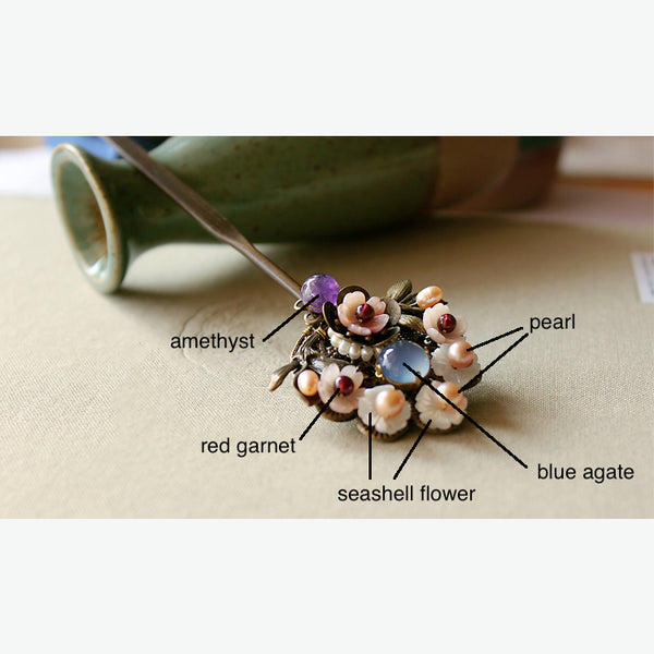 details of the hair stick: it is decorated with blue agate, red garnet, pearls, amethyst, and seashell flowers