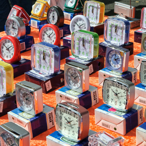 Photo of colorful clocks on an orange table
