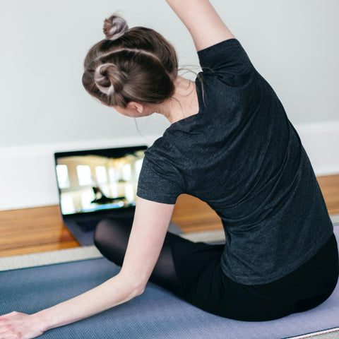 Unsplash image of woman doing yoga at home in front of her laptop