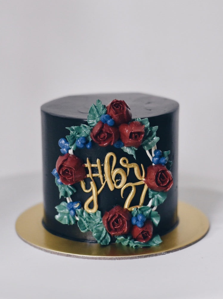 Black cake with roses and wreath in name
