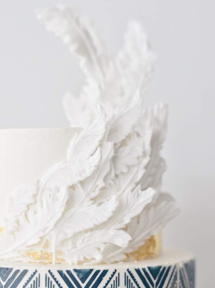 geometric two tier cake with white feathers -Zee & Elle