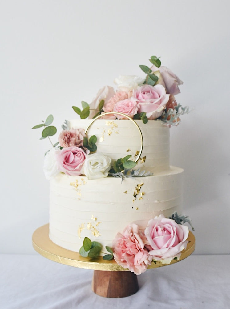 Two tier white cake with gold foil and pink flowers with gold ring-zeeandelle