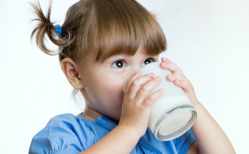 Toddler drinking milk from a glass