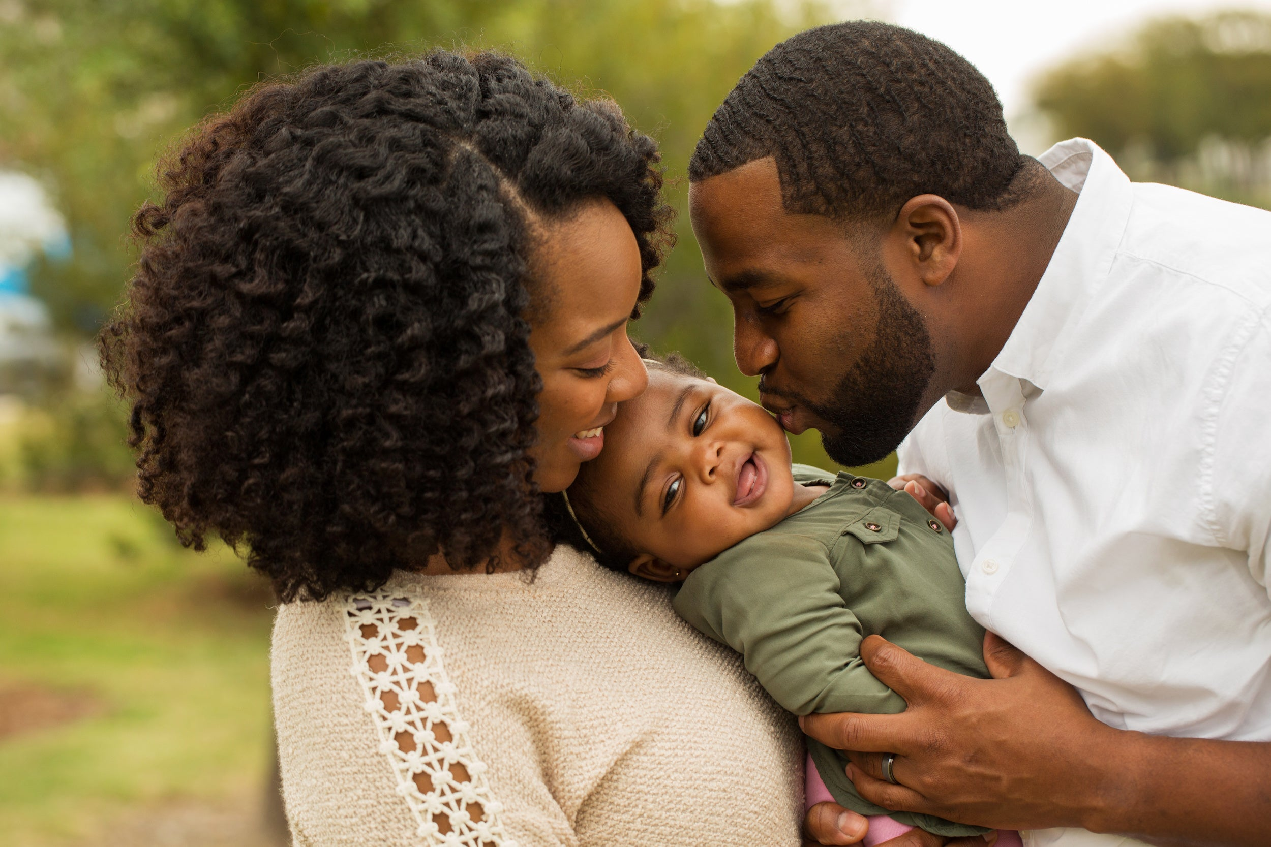Happy family hugging and kissing toddler while enjoying the outdoors