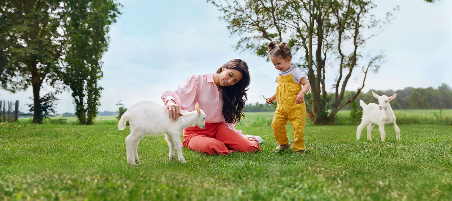 Woman petting goat beside happy toddler