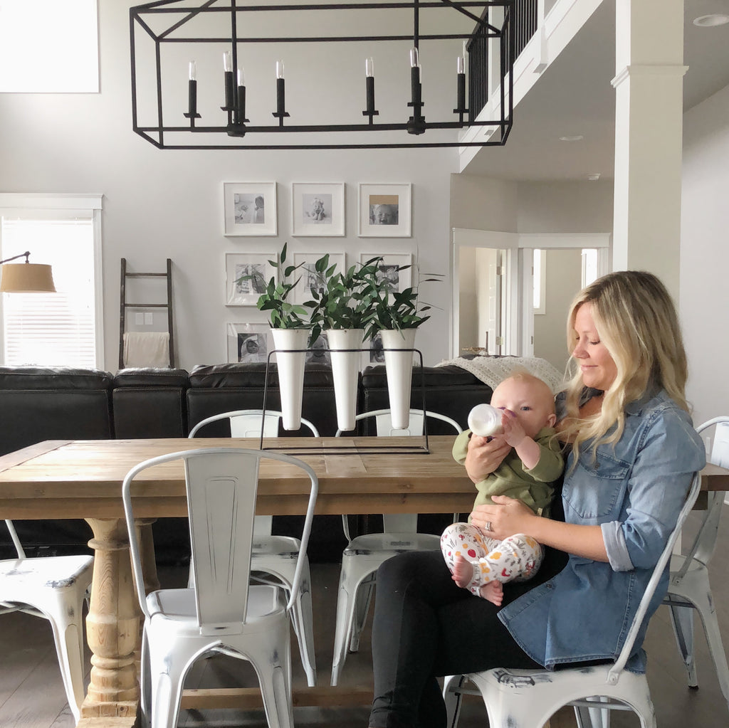 Mom bottle feeding her daughter at dining room table