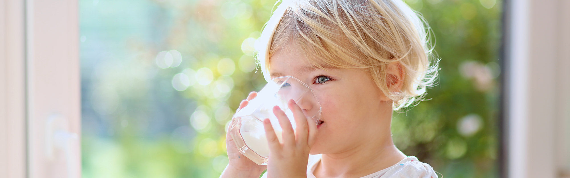 blond toddler drinking a glass of milk