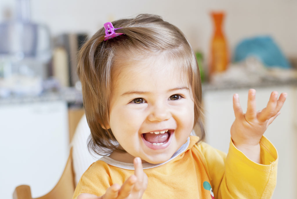 Smiling toddler raising her hands with joy