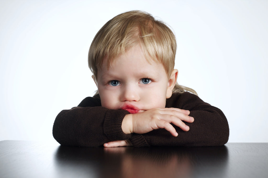 Blond haired toddler boy pouting with crossed arms