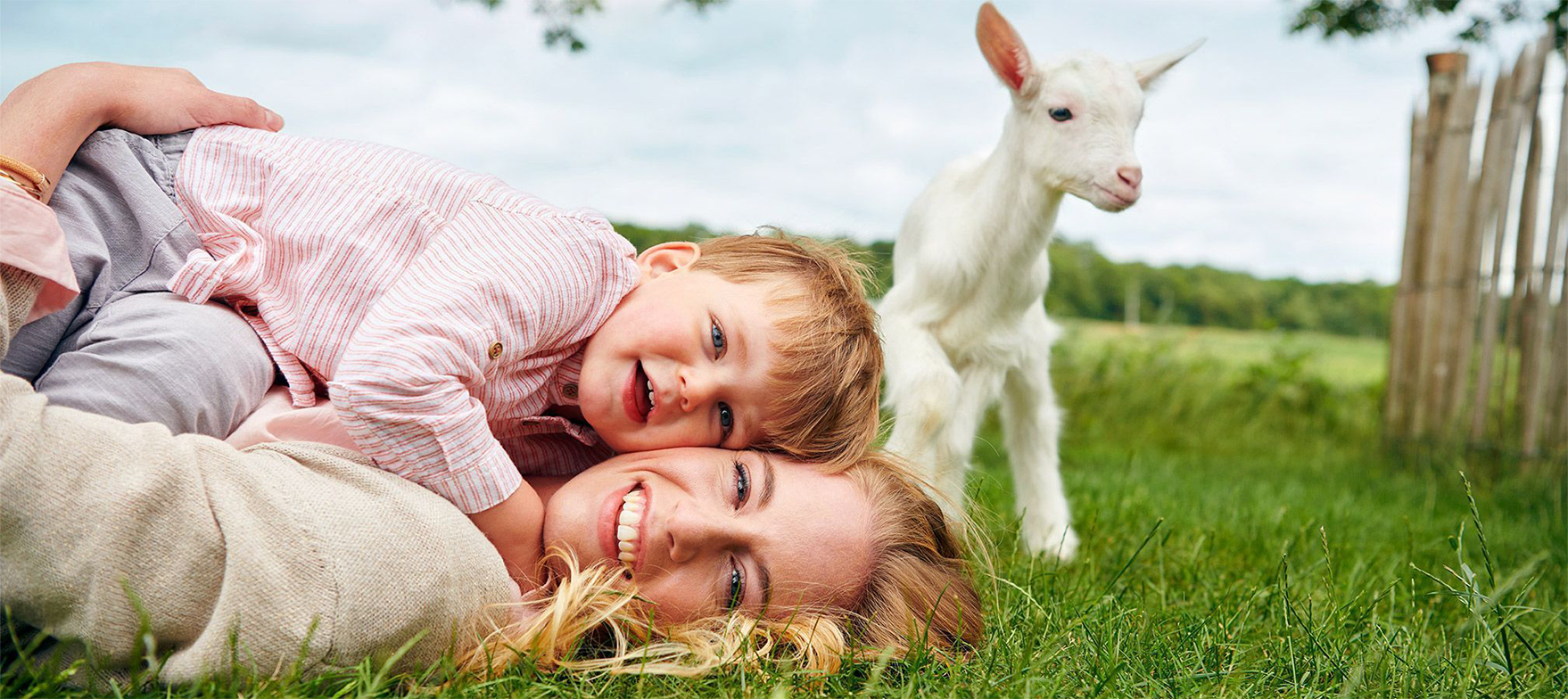 Mom and child laying in grass with baby goat looking on