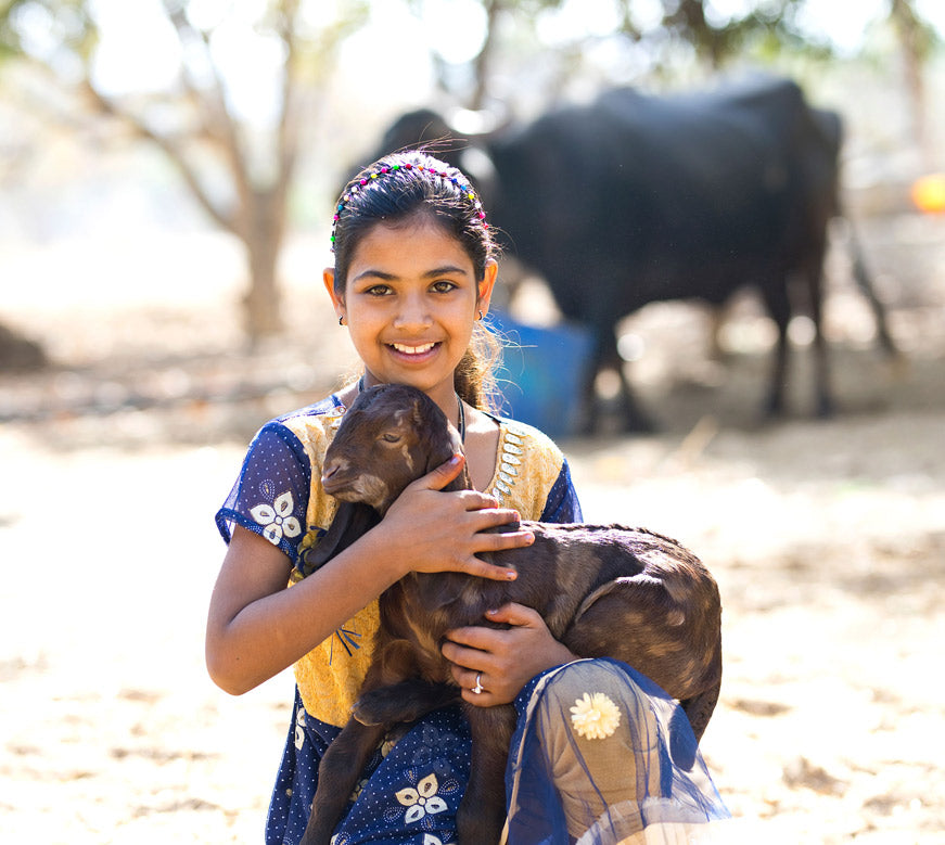 Young woman holding a goat