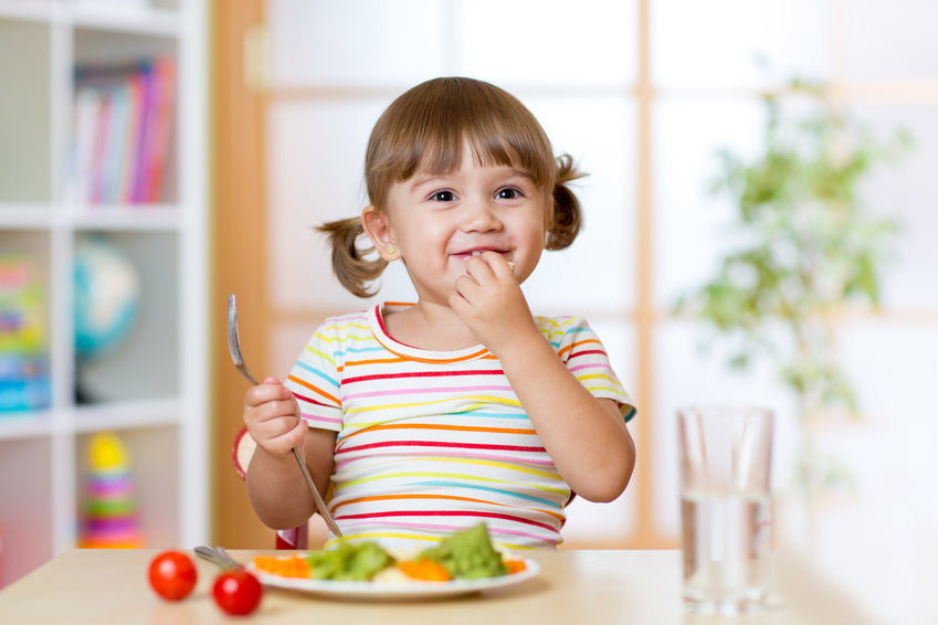 Toddler girl sitting at table eating vegetables and smiling