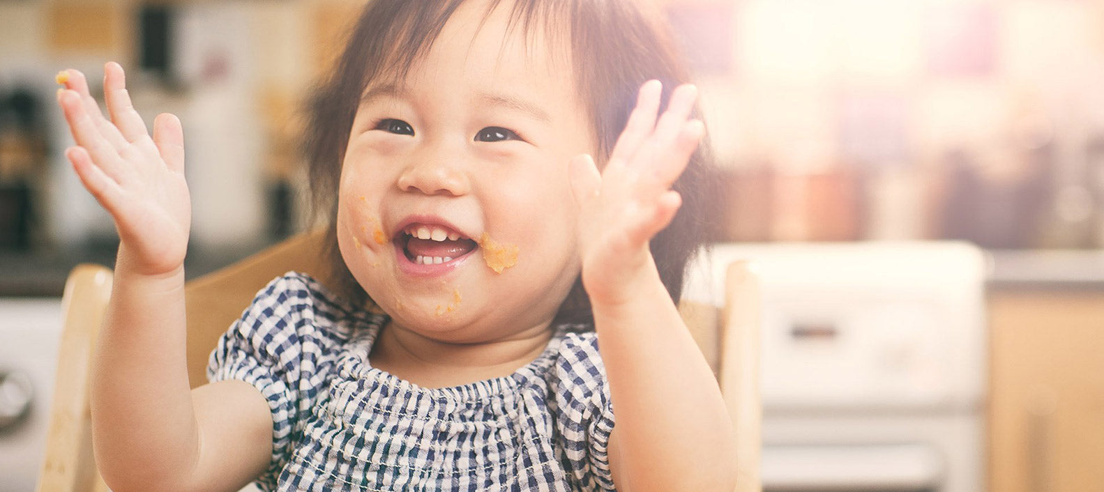 child with food on face smiling and holding up hands