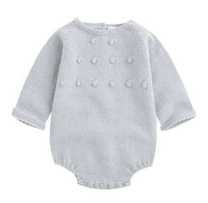 light misty green knit baby onesie. Long-sleeved with puff ball details on front and button closure in back and underneath.