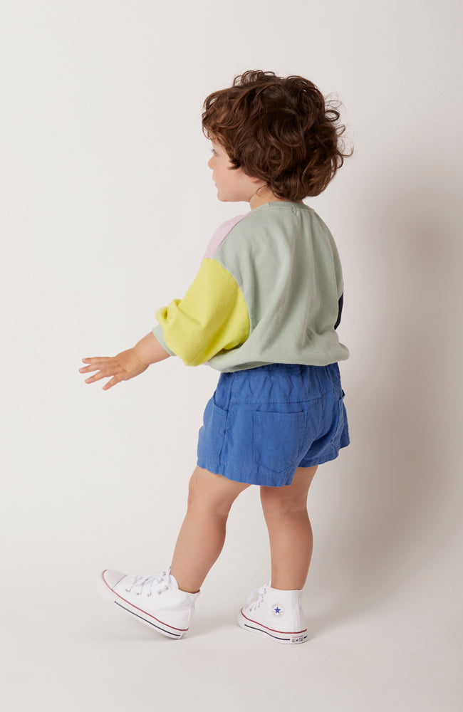Max shorts in blue with front and back pockets with yoke detail for babies and kids front view