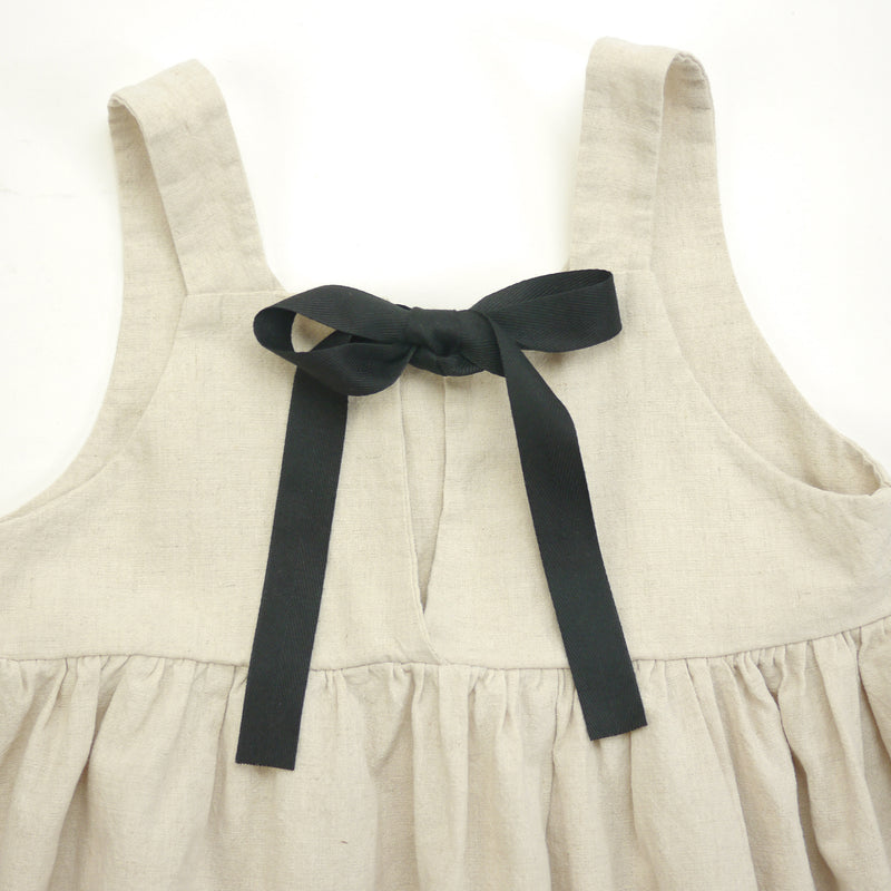 Isabelle sleeveless dress in beige with contrasting black ribbon ties for kids back bow detail