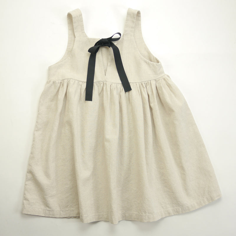 Isabelle sleeveless dress in beige with contrasting black ribbon ties for kids full back view