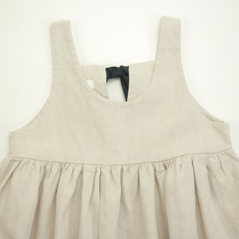 Isabelle sleeveless dress in beige with contrasting black ribbon ties for kids front neckline view