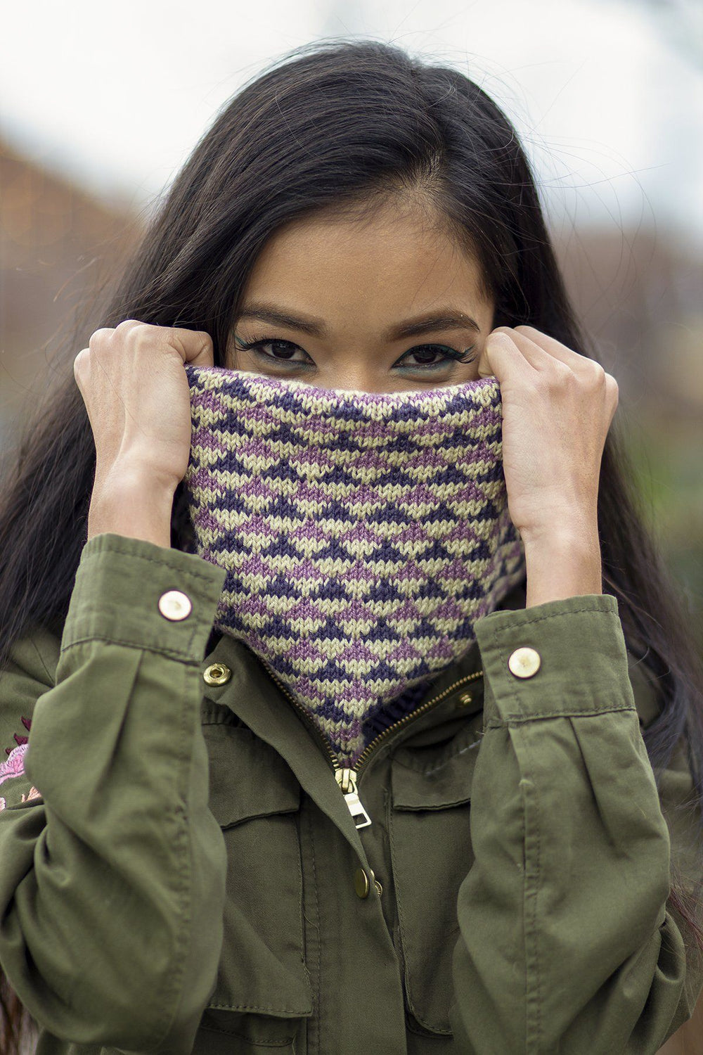 dark haired model holding cowl with colored triangle pattern over her lower face with only her eyes showing