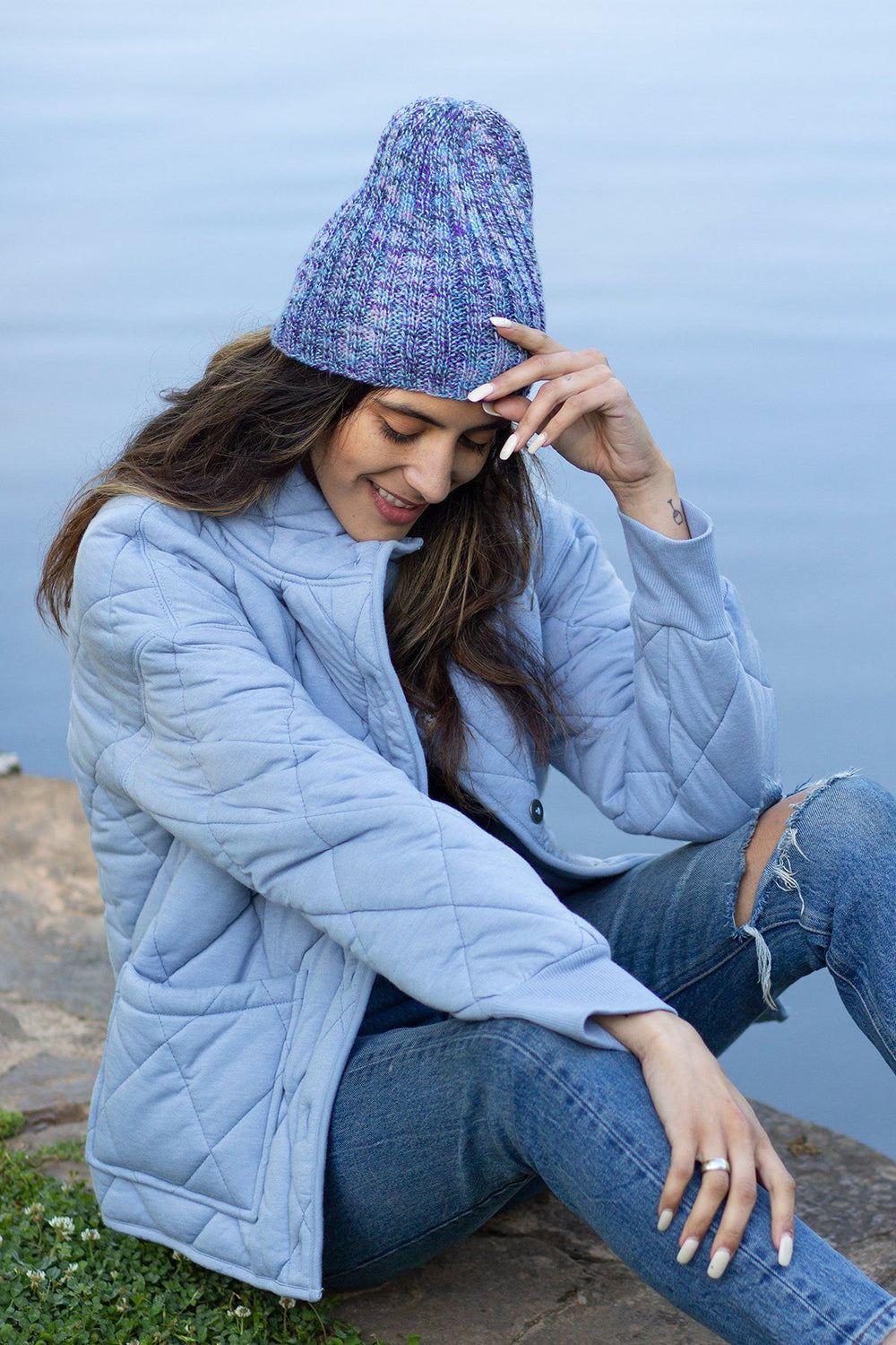 a tanned woman with long brown hair, thick eyebrows, and long white nails sits on the stone at the edge of a body of water. She's wearing a light blue down jacket, blue jeans, and a marled blue handknit ribbed hat. She's leaning her left elbow on her bent knee and touching the brim of the hat with the same hand. Her right hand is resting on her right calf.