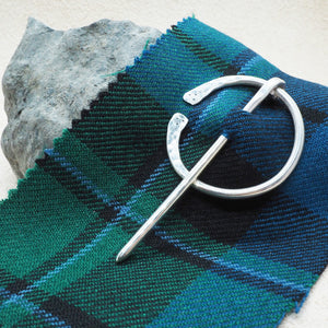three mm sterling silver kilt pin brooch and dksilver displayed on a peace of tartan  dksilver artisan Scottish Silver made by Daniel Killeen jewellery accessories for men bracelets, cuffs, kilts pins and contact for bespoke service