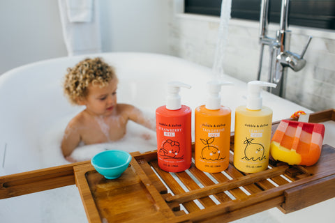 boy in tub looking at three bottles of bubble bath