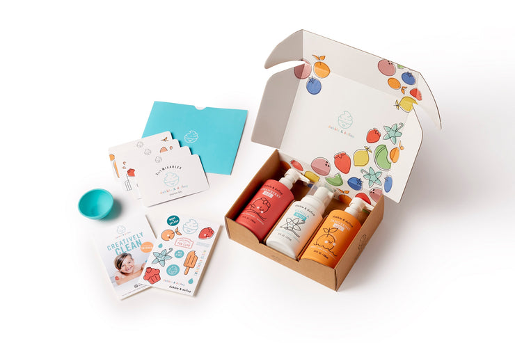 Three bottles of shampoo, bubble bath and body wash nested in custom branded box. Included outside box are recipe cards, temporary tattoos and a small mixing bowl.