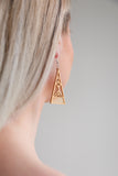 Aadra Collection Wooden Arrow gold painted earrings on a models ear