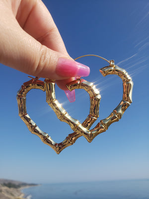 Women's hand with Pink long nails holding Super Light & Thin Gold Plated Heart Bamboo Hoop Earrings. Background at a beach scenery. most of the picture is a beautiful blue gradient sky with a slight view of the beautiful blue ocean and an even slighter view  on the left size corner of the California 101 freeway coastline.