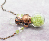 small glass bottle with raw peridot and faceted crystal
