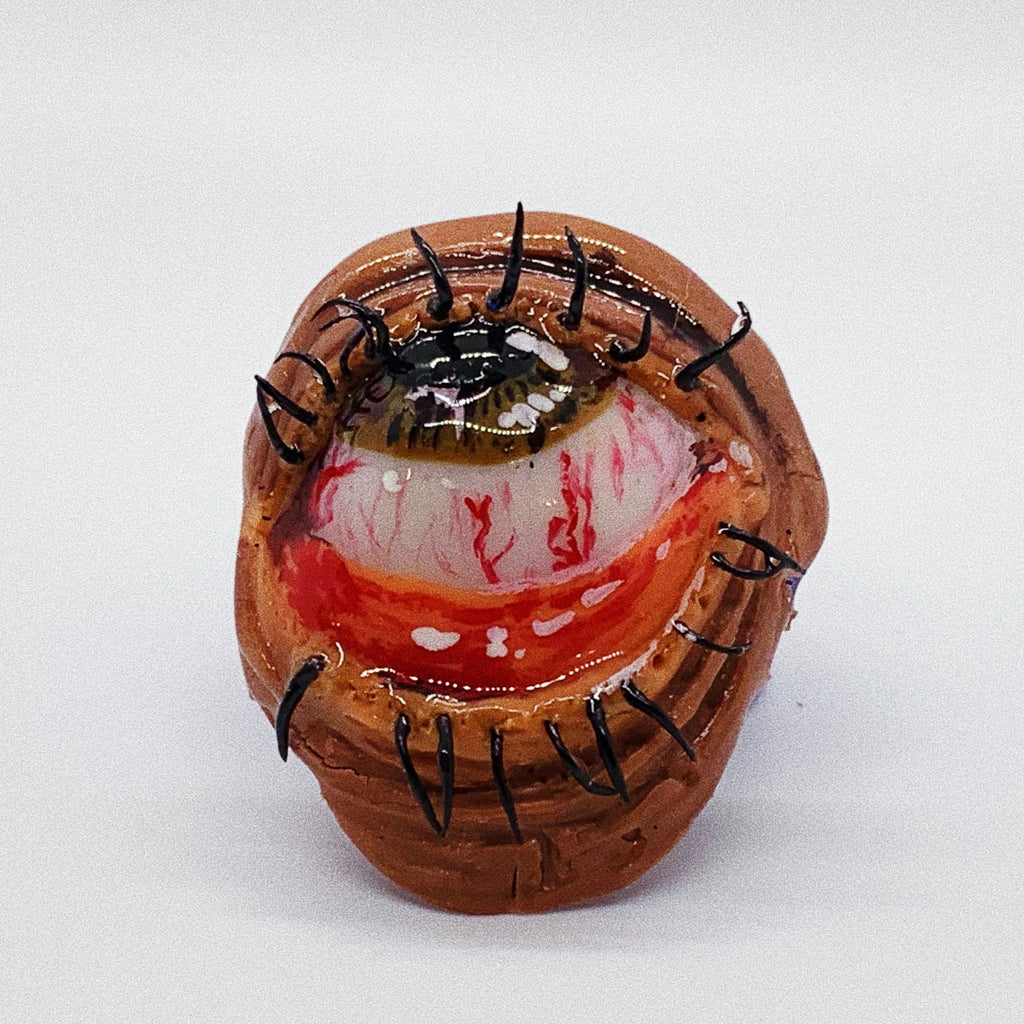 brown eye rolling back into it's head, with their bottom eyelid pulled down exposing the pink flesh. Made of polymer clay and coated with resin