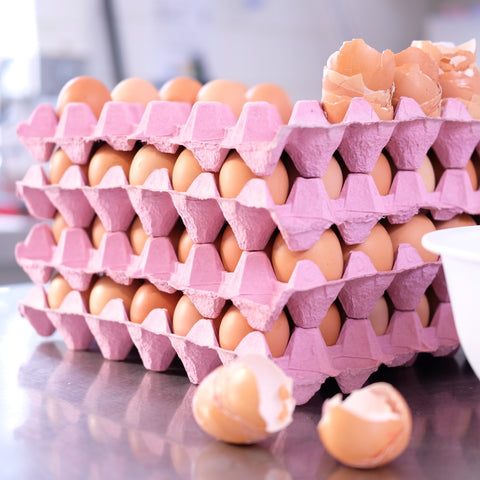 Free Range Eggs stacked in pink trays for baking