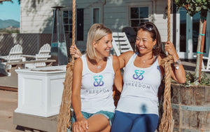 Two women sitting on a swing wearing Flow 2 Freedom White Aspire bamboo logo tank tops