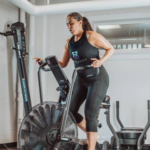Woman on elliptical wearing black Exhale cropped leggings