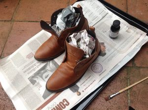 newspaper in leather boots