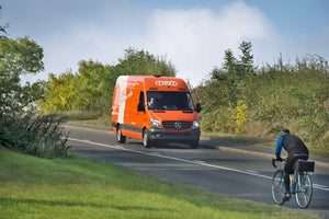 TNT Mercedes Benz delivery van with bicycle on opposite side of the road