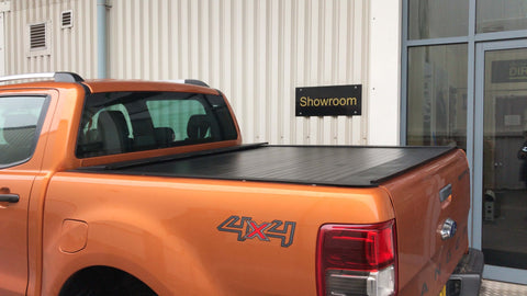Direct4x4 remote-controlled roll and lock style shutter pick up truck load be tonneau cover on an orange Ford Ranger.