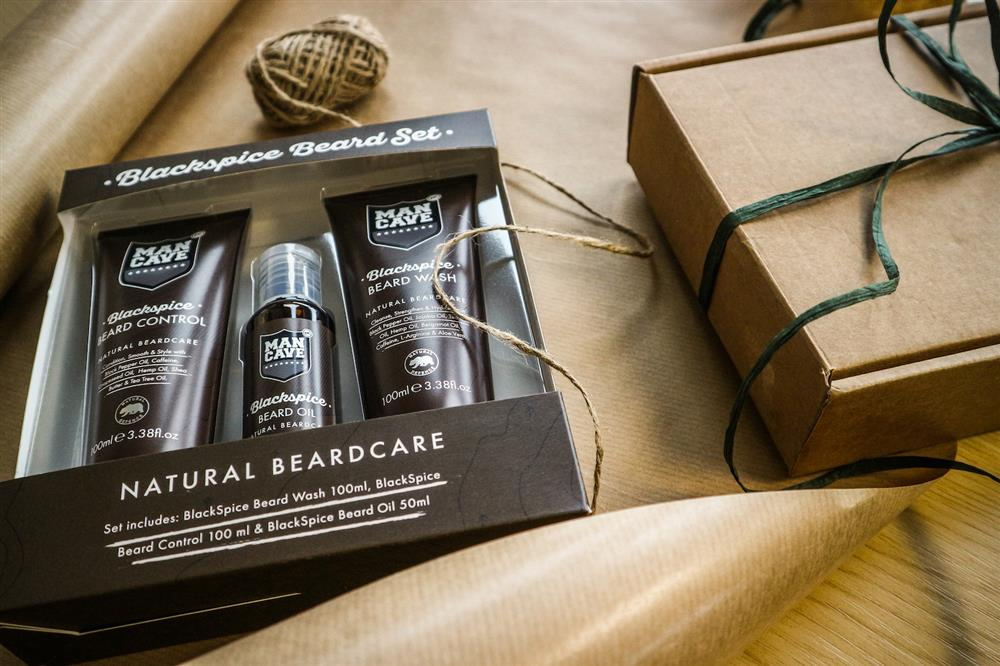A ManCave Blackspice Beard Set containing (from left to right) a Blackspice Beard Control, Blackspice Beard Oil and a Blackspice Beard Wash laying on a table top with brown wrapping paper and ribbon