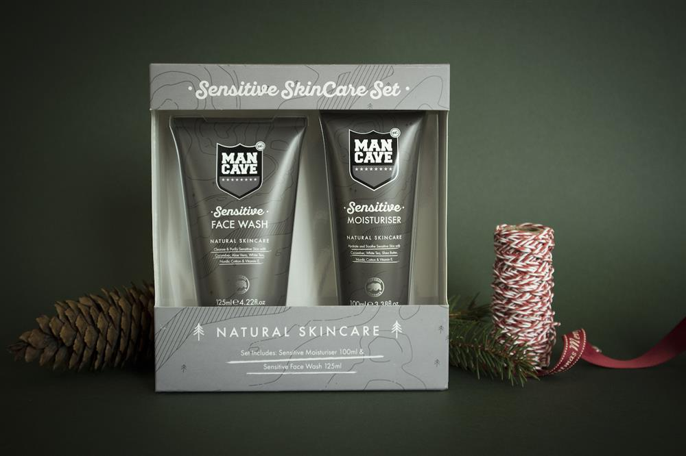 A ManCave Sensitive Gift Set containing a Sensitive Face Wash and a Sensitive Moisturiser on a green background with pine cones and ribbon