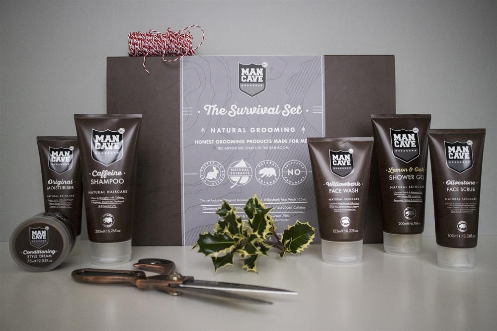 A ManCave Survival Set containing (from left to right) a Conditioning Style Cream, an Original Moisturiser, a Caffeine Shampoo, a Willowbark Face Wash, a Lemon and Oak Shower Gel and an Olivestone Face Scrub. All on a grey background with a pair of scissors and a piece of Holly.