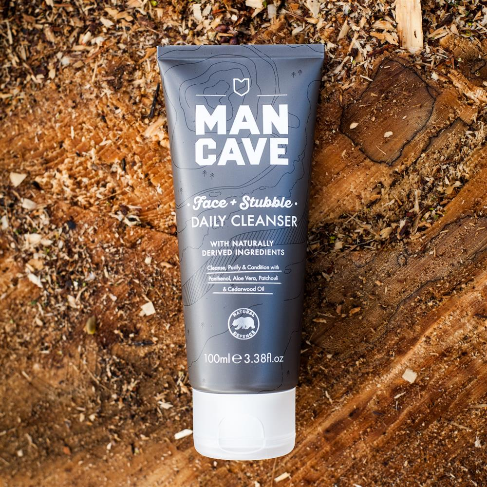 A ManCave Face and Stubble Cleanser on a tree stump with wood shavings