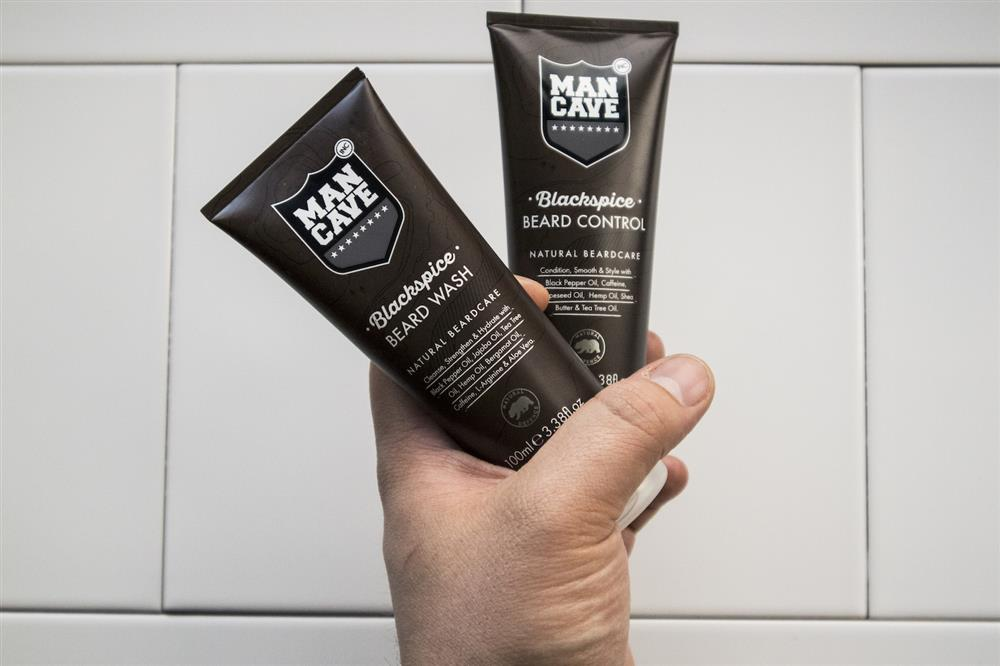 A set of two ManCave products: Blackspice Beard Wash and Blackspice Beard Control held in a man's hands on a white tiled background