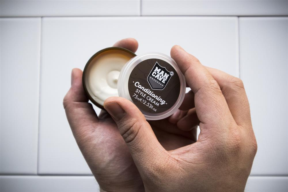 A ManCave Conditioning Style Cream being opened by a man's hands on a white tiled background