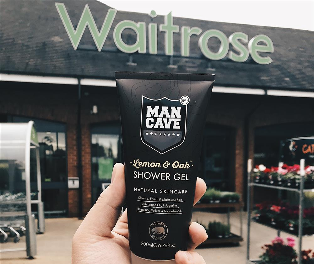 A ManCave Lemon and Oak Shower Gel held with mans hand in front of a Waitrose Store front