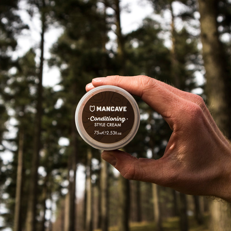 ManCave conditioning style cream 75ml being held by a mans hand with greenery and trees in the background