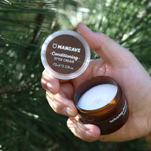 ManCave conditioning style cream 75ml being held by a mans hand in front of greenery