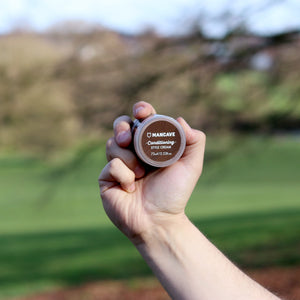 ManCave conditioning style cream 75ml being held by a mans hand with a green field in the background