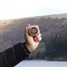 ManCave conditioning style cream 75ml being held up by a mans hand with water and a lavender hillside in the background