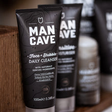ManCave face and stubble daily cleanser 100ml in a 100% recyclable grey tube on a wooden bathroom shelf with a selection of other mancave products in the background