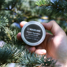 ManCave intense hydration moisturiser 100ml black tub being held by a mans hand in front of a green bush